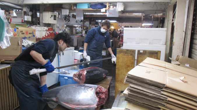 Two guys butchering a pair of $4,000 tunas at the Tsukiji Fish Market in Tokyo.