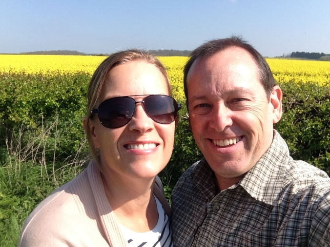 The loving couple next to the yellow field.